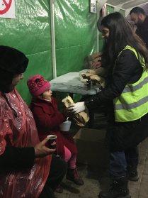 Volunteer feeding refugee child