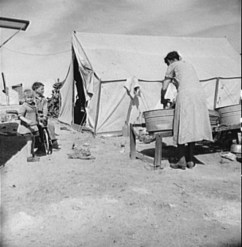 Dust Bowl refugee woman washing clothes in California migrant camp. 1937. Photo by Dorothea Lange.