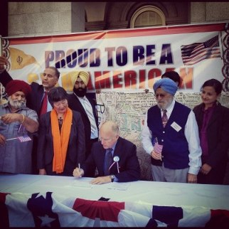 California Governor Jerry Brown (seated) signs AB1964 and SB1540 into law at a rally at the California State Capitol last Saturday. Assembly Member Mariko Yamada (standing left of the Governor), Dr. Onkar Bindra (standing right of the Governor) and Sikh Coalition Advocacy Manager Simran Kaur (far right) joined the Governor. (source: Instagram user i2theb)
