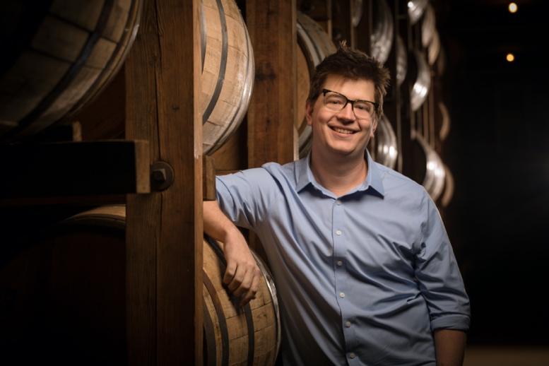 Matt Greeno stood in the rickhouse with barrels