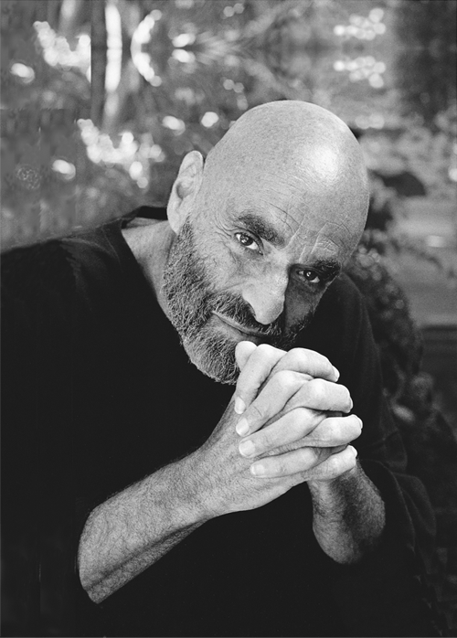 Black and white photo of Shel Silverstein clasping his hands and leaning forward. Photo by Larry Moyer