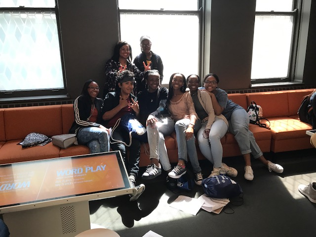 A group of students poses for a photo on couches in the American Writers Museum in Chicago, IL