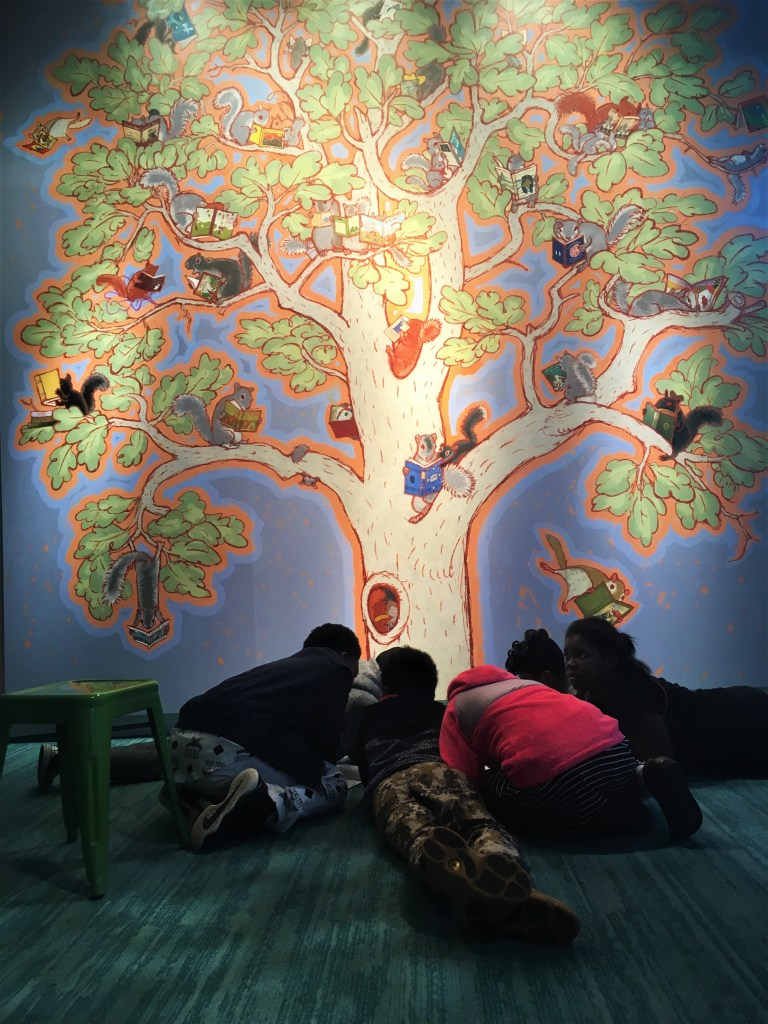 Children working at the base of Paul O. Zelinsky's mural of a tree