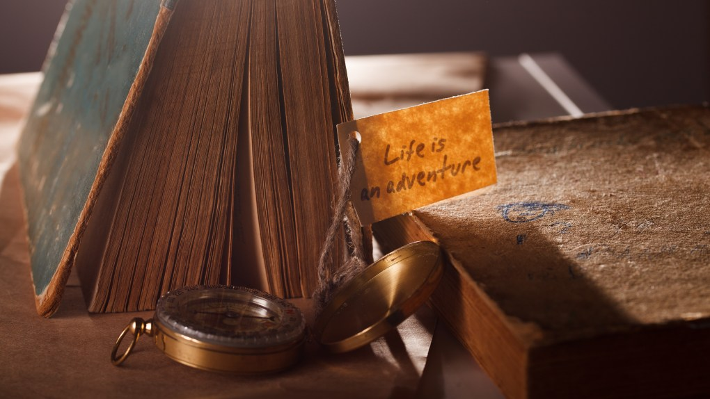 "An old book and open compass with the label ""life is an adventure"""