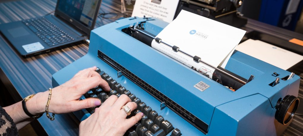 A visitor's hands typing on a large blue IBM typewriter at the American Writers Museum
