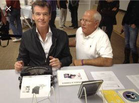 Pierce Brosnan types on John Lennon's typewriter, photo courtesy of Steve Soboroff