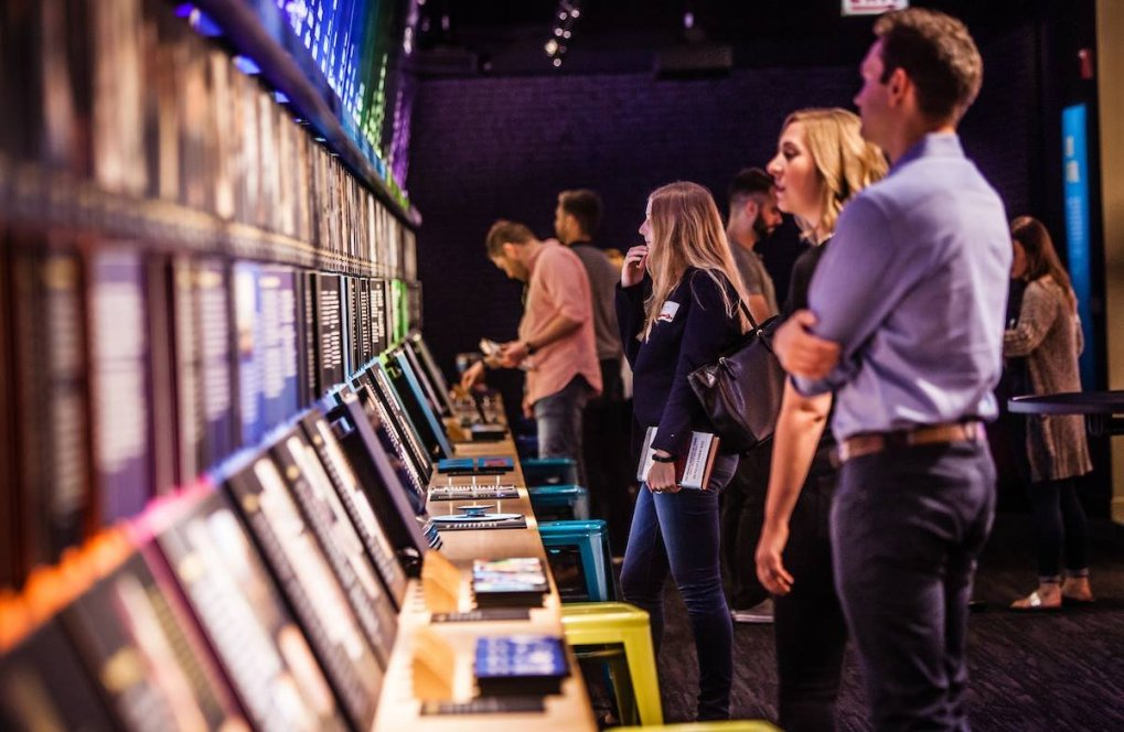 A group of visitors interact with the American Voice timeline in the Nation of Writers Gallery at the American Writers Museum in Chicago, IL. A blonde woman in a black sweater in the middle ground is the focus of the photo.