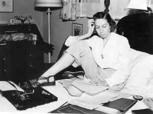 Eudora Welty at work writing on her bed with typewriter