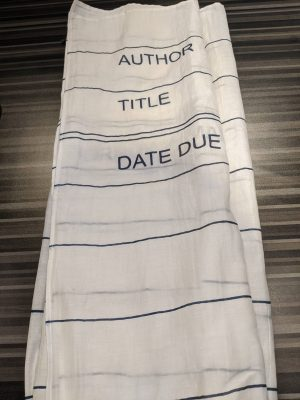 """A white scarf with a design to resemble an old library card. Features black lines and the words """"Author"""" """"Title"""" """"Date Due"""" at one end. Thin, somewhat sheer material."""