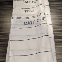 "A white scarf with a design to resemble an old library card. Features black lines and the words ""Author"" ""Title"" ""Date Due"" at one end. Thin, somewhat sheer material."