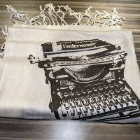 A white scarf with a black silkscreen design of an Underwood typewriter on it.