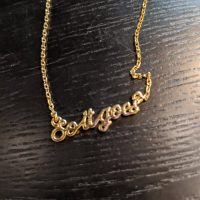 """A gold necklace with pendant words reading """"So it goes"""""""