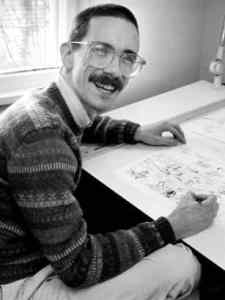 Photo of Bill Watterson drawing at desk and smiling