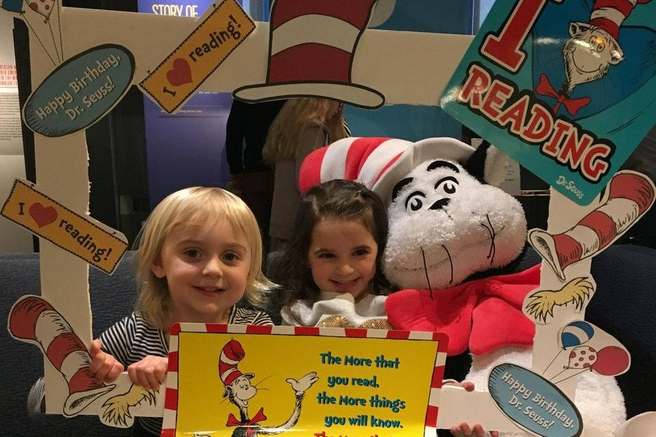 """Two children pose on a couch at the American Writers Museum holding a frame that has The Cat in the Hat and """"I love reading"""" written on it."""