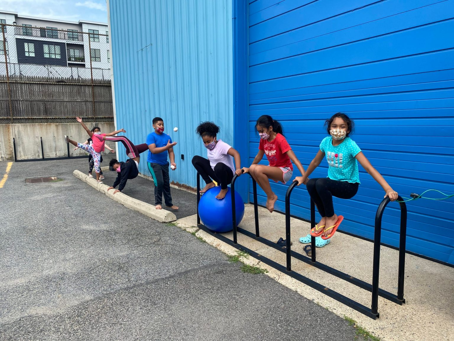 seven kids doing acrobatics and hanging on a bike rack outside of a warehouse