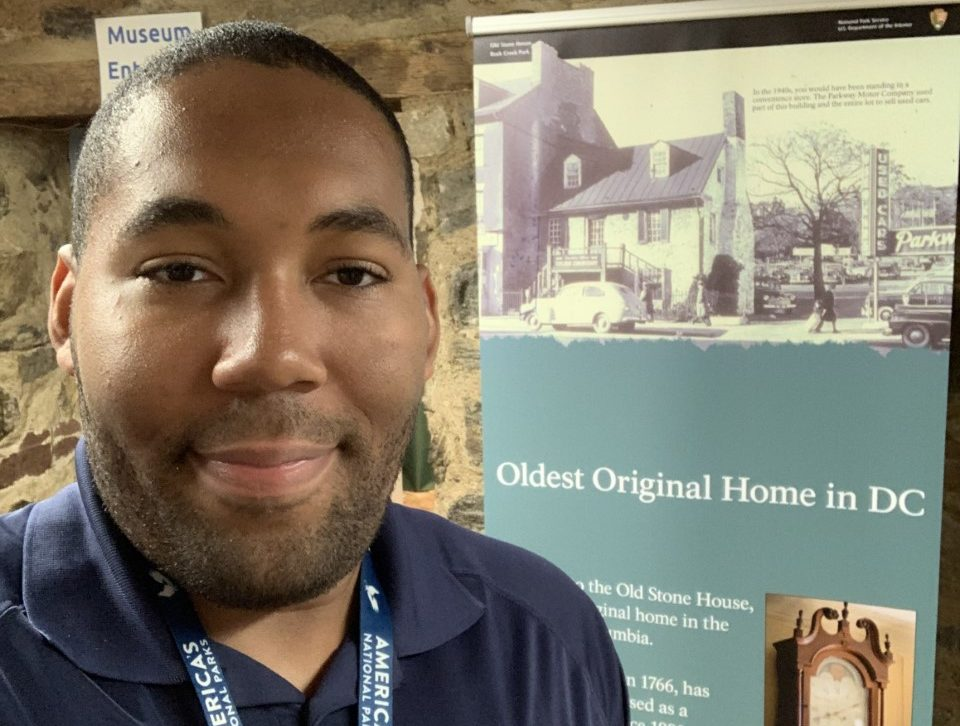 "Arkile J. poses in front of the museum entrance at Old Stone House in Rock Creek Park. An informational sign behind him is titled ""Oldest Original Home in DC"""
