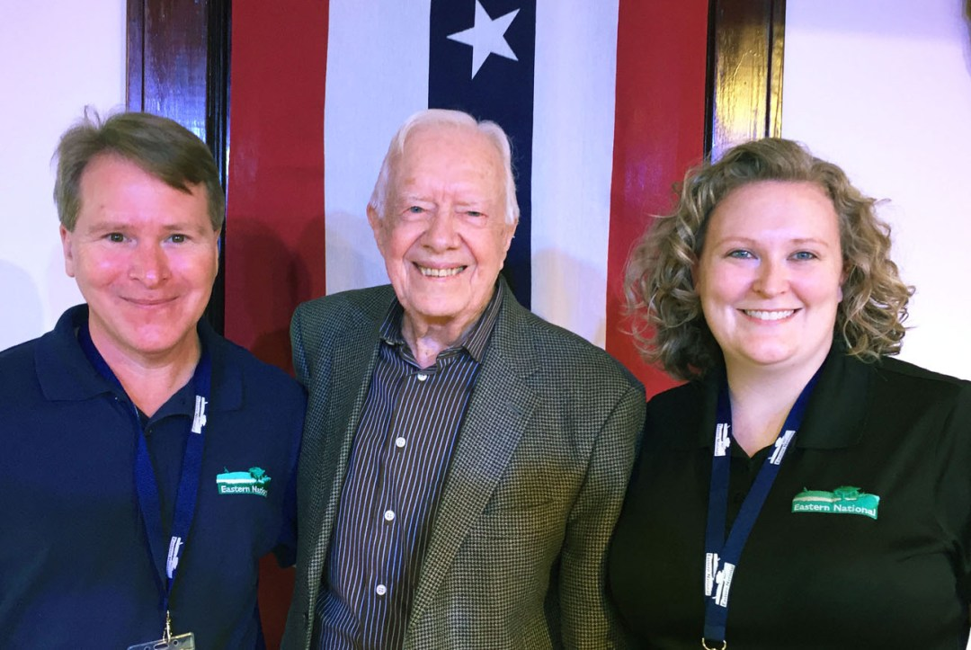 Former President Jimmy Carter stands with EN employees Carly Koch and John Kelton