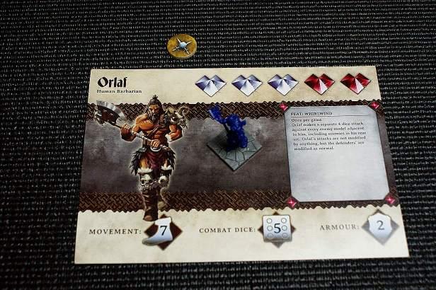 De setup voor Orlaf de Barbaar. Niet veel meer dan een miniatuurtje, een overzichtskaart met belangrijke statistieken én een activatie fiche. Op de kaarrt staan onderandere de movement (7), het aantal combat dice (5) en wanneer Orlaf injured raakt (3 hits (de witte hartjes)).