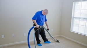 Man steam-cleaning a carpet in an empty room