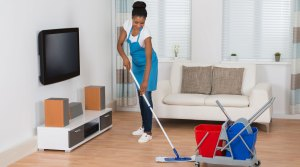 Woman cleaning hardwood living room floor