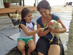 Photo of woman holding a chicken while a young girl feeds it Cheerios