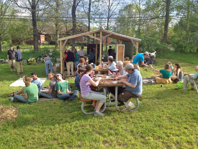 Photo of large group of people eating outside at picnic tables and sitting on the ground