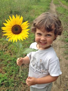 Photo of young child smiling and holding a large sunflower