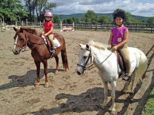 Photo of two young girls riding ponies.