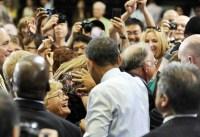 US President Barack Obama helps to preve