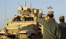 United States military officers welcome vehicles entering Kuwait during their withdrawal from Iraq