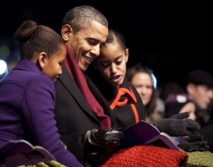 US President Obama and his daughters look at the program during the lighting of the National Christmas Tree in Washington