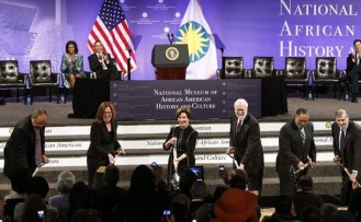 U.S. President Obama and first lady Michelle watch the ceremonial ground breaking for the Smithsonian National Museum of African American History and Culture in Washington