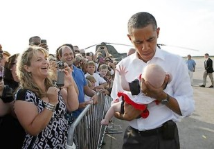 U.S. President Obama holds a baby after landing in Buzzard's Bay before boarding Marine One to take him to Martha's Vineyard in Massachusetts