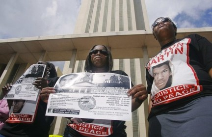 Women wear shirts and hold up signs at the Florida Capitol during a rally, organized by the National Christian League of Councils, for slain teen Martin in Tallahassee