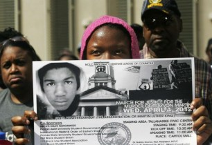 A young participant watches a speaker from behind a sign during a rally organized by the National Christian League of Councils for slain teen Martin in Tallahassee