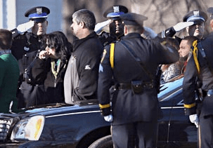 a police honor guard salutes at the funeral of Victoria Soto
