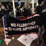 "Protester holds up an American flag with a sign that reads ""No Allegiance to White Supremacy"" outside Terminal 4 of Kennedy Airport Saturday night as throngs of people assembled outside the airport and the Brooklyn Federal Courthouse to demonstrate against President Trump's travel ban on selected Muslim countries."