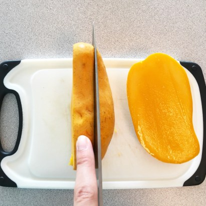 Note: this is NOT how to hold a mango. I was trying to demonstrate how thick the center cut containing the pit should be. I only have one set of hands to cut and take pictures, so be careful!