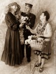 Madwoman (Janice Hansen) receives a boa from Doorman (Howard Davis) and a flower from the Flower Girl (Maureen Lukie)