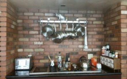 image of brick above the stove before faux cement tile backsplash