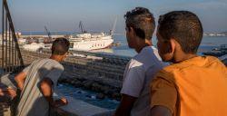 Tres chicos, que viven en la calle, observan los barcos del puerto de Melilla.