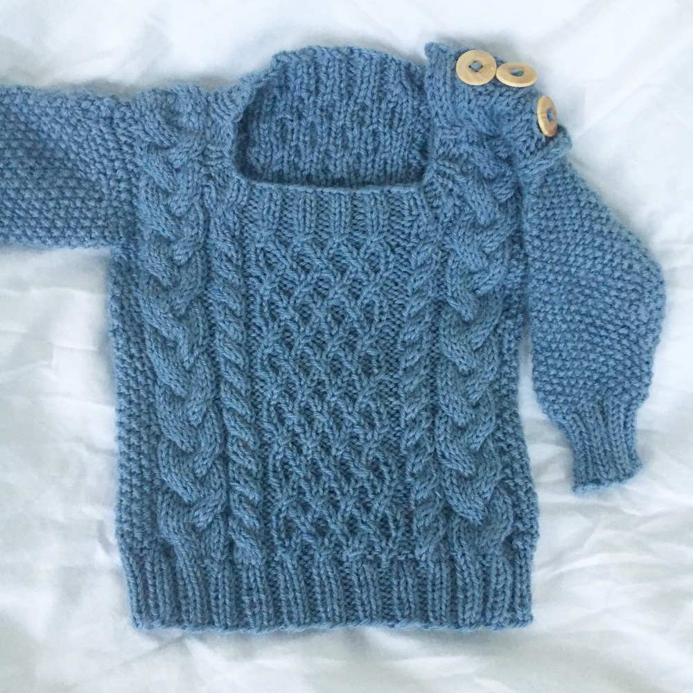 A sweet and cabled blue baby aran sweater