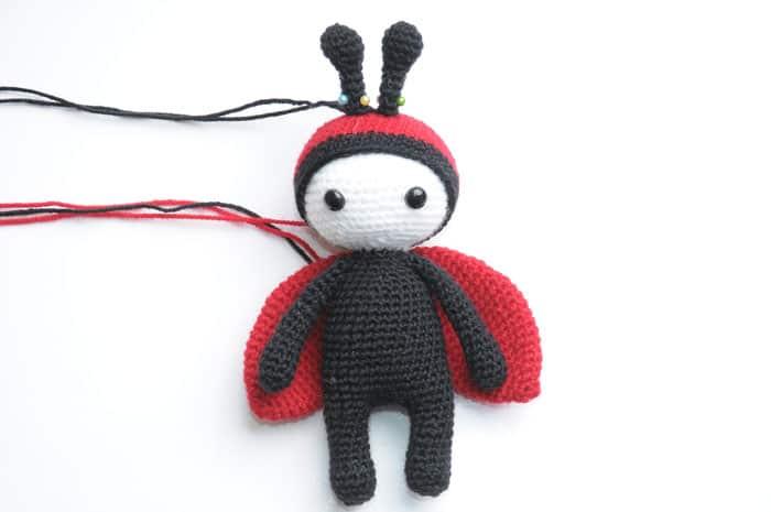 Amigurumi baby doll in ladybug costume