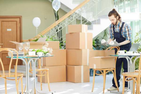 young-mover-unpacking-boxes-in-new-restaurant-EQYNVSX.jpg
