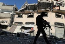 Un homme armé palestinien marche près de l'appartement de Baha Abou al-Atta, haut commandant du groupe Jihad islamique, après la frappe israélienne visant ce dernier