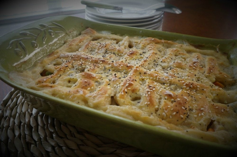 Homemade Chicken Pot Pie: Tender chicken and vegetables swim together in a creamy sauce that is adorned with a flaky homemade biscuit crust.: