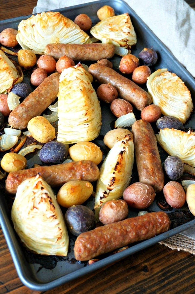 Bratwurst Sheet Pan Dinner: Bratwurst, potatoes, onions, and cabbage are roasted with a mustard maple vinaigrette for an easy, flavorful one pan meal.