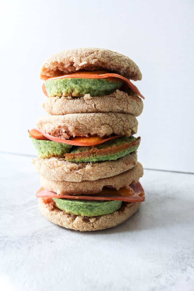 """Green Eggs and Ham Breakfast Sandwiches: Naturally """"dyed"""" with spinach eggs are paired with ham and sharp cheddar cheese to create a breakfast sandwich."""