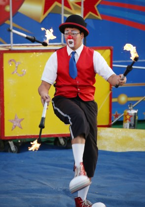 """Circus performer """"Franko"""" juggles three flaming batons during a performance by NoJoe's Circus at the Boyle County Fair Wednesday evening."""