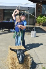 Rodeo rider, Alexis Laughlin, right, helps Anne Conyers, of Jacksonville, Florida, learn how to lasso a plastic steer hear during the Farm/City Festival Saturday. (Photo by Robin Hart)